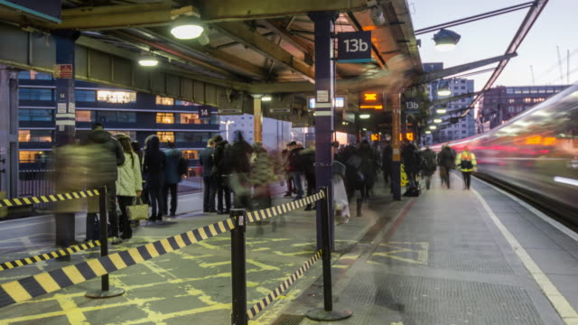 stockvideo's en b-roll-footage met hazard barriers control a constant flow of rapidly moving commuters arriving on the station platform and wait for trains during the start of the evening rush hour at manchester piccadilly station - perron