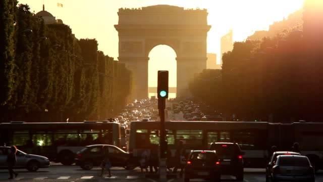 a haze covers traffic and pedestrians near the arc de triomphe. - arc de triomphe paris stock videos & royalty-free footage