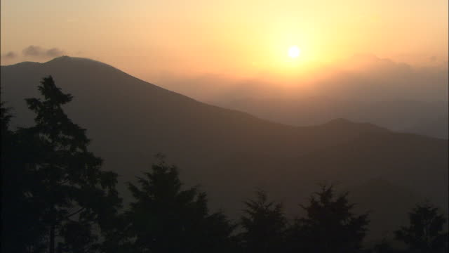 a haze fills the golden hour sky over silhouetted mountains. - nara prefecture stock videos & royalty-free footage