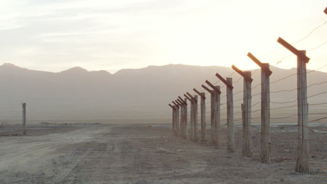 a haze hovers over mountains near a prison camp. - barracks stock videos & royalty-free footage