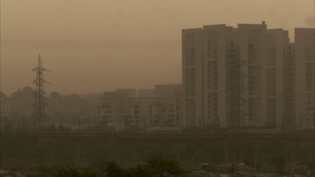 Haze obscures a train passing a tall building in Delhi, India.