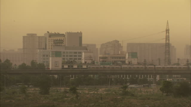 Haze obscures an elevated train passing tall buildings in Delhi, India.
