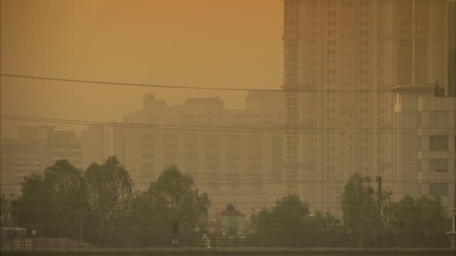 Haze obscures tall buildings in Delhi, India.