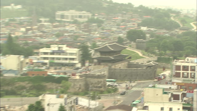 a haze settles over hwaseong fortress and the city of suwon, south korea. - hwaseong palace stock videos and b-roll footage