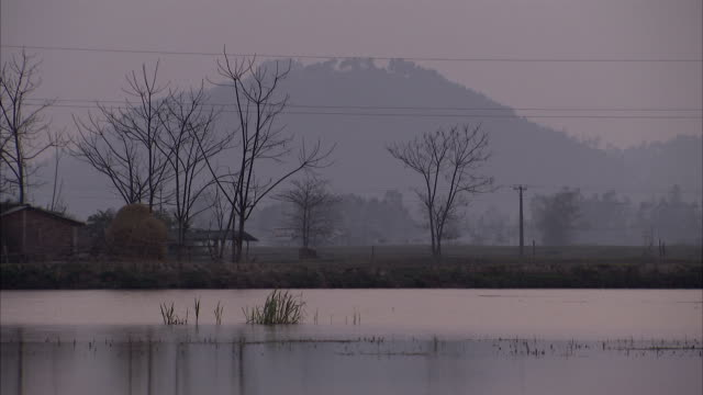 a haze shrouds a mountain far in the distance beyond a lake. - seeufer stock-videos und b-roll-filmmaterial