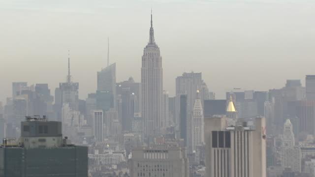 a haze shrouds the empire state building and the manhattan skyline. - manhattan video stock e b–roll