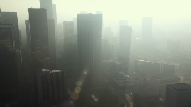 haze surrounds the skyscrapers in the financial district of downtown los angeles. - smog stock-videos und b-roll-filmmaterial