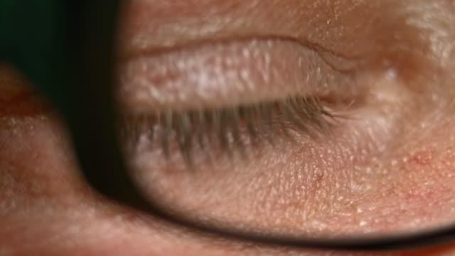 vídeos de stock e filmes b-roll de ecu olhando através dos óculos olhos castanhos claros - primeiríssimo plano
