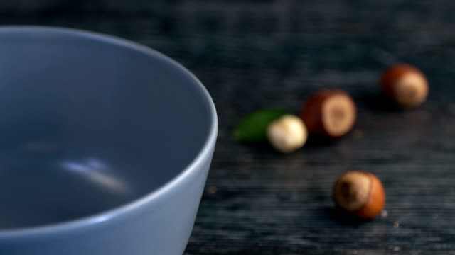 hazelnuts are poured out of it on wooden background slow motion - nutshell stock videos and b-roll footage