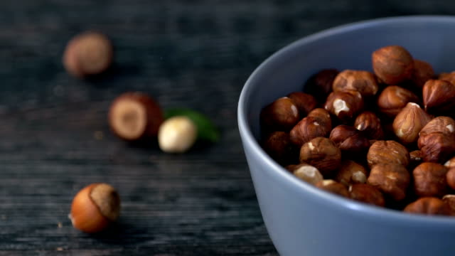 hazelnuts are poured out of it on wooden background - nutshell stock videos & royalty-free footage