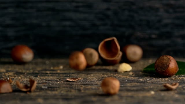 ヘーゼル ナッツは、木製の背景にそれを注がれる - ナッツの殻点の映像素材/bロール