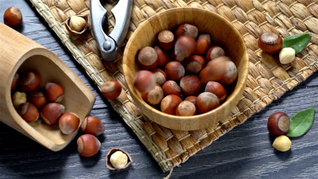 hazelnuts falling into wooden bowl, slow motion - nutshell stock videos & royalty-free footage