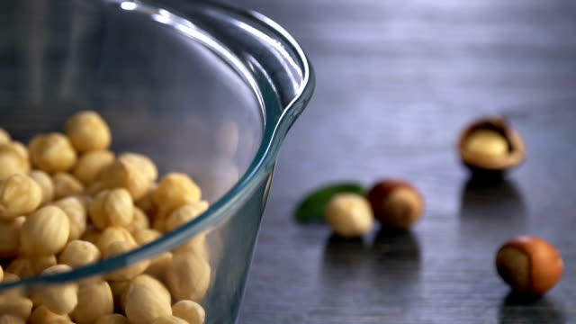 hazelnuts falls from high into the bowl, slow motion. - nutshell stock videos & royalty-free footage