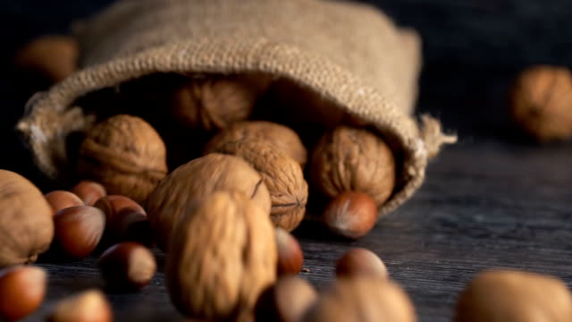 hazelnuts pour out of falling sack on table, slow motion - sack stock videos & royalty-free footage