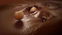 Hazelnuts Splashing Into Liquid Milk Chocolate in 4K Super slow motion