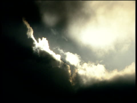 Hazy beams of sunlight burst through gathering rain clouds Swiss Alps