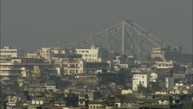 ws pan hazy cityscape with howrah bridge in background/ calcutta, india - howrah bridge stock videos & royalty-free footage