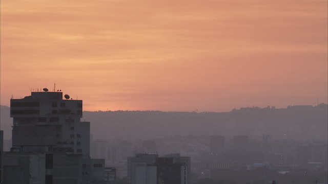 WS Hazy orange sunset over Caracas high rises / Metropolitan District of Caracas, Miranda, Venezuela