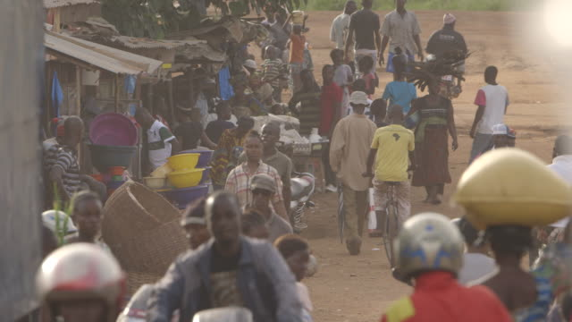 Hazy sequence showing a busy road running through a market in Kenema, Sierra Leone.