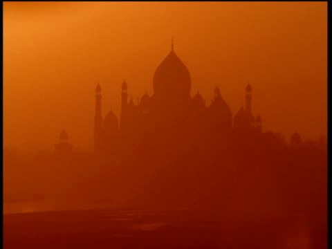 hazy silhouettes of taj mahal against rich orange sky agra - agra stock videos and b-roll footage