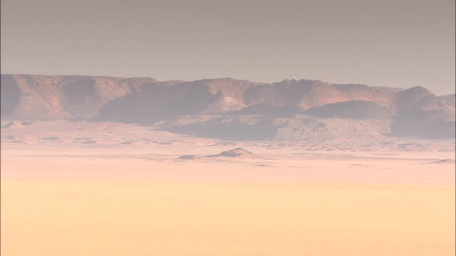 a hazy sky surrounds the desert and distant mountains. - heatwave stock videos & royalty-free footage