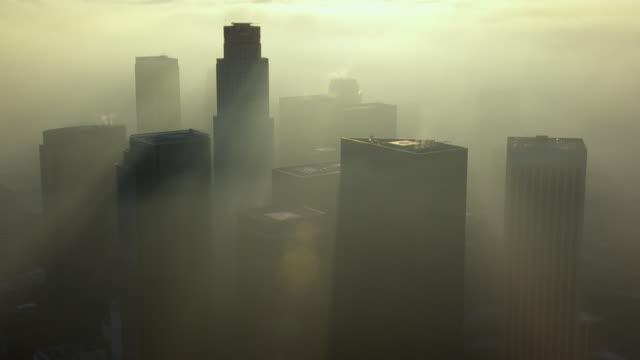 vídeos de stock, filmes e b-roll de a hazy smog surrounds the skyscrapers of downtown la, california. smog remains a serious health threat to inhabitants of the los angeles area. - ominoso