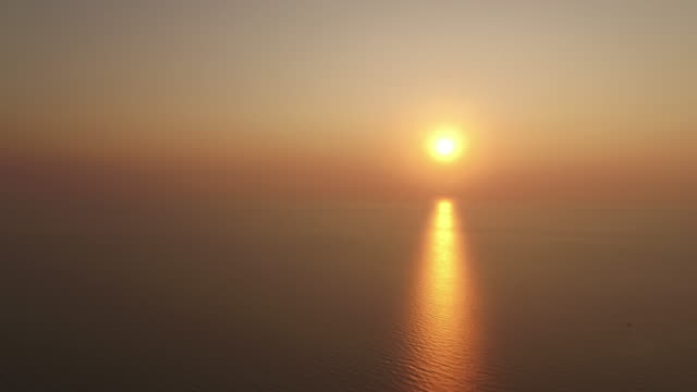 a hazy sun during an amazing sunrise casts golden light across the rippling water in pranburi, thailand - varmt ljus bildbanksvideor och videomaterial från bakom kulisserna