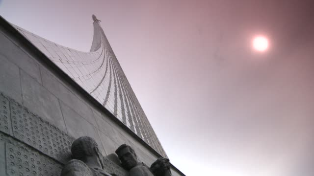 a hazy sun glows above the sputnik monument in moscow. available in hd. - sputnik stock videos & royalty-free footage