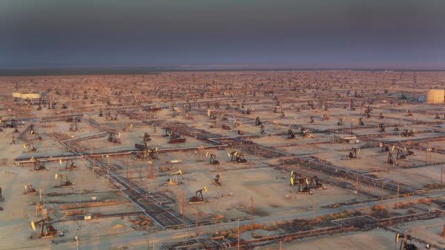 hazy sunset in vast oil field in missouri triangle, ca - drone shot - industria petrolifera video stock e b–roll