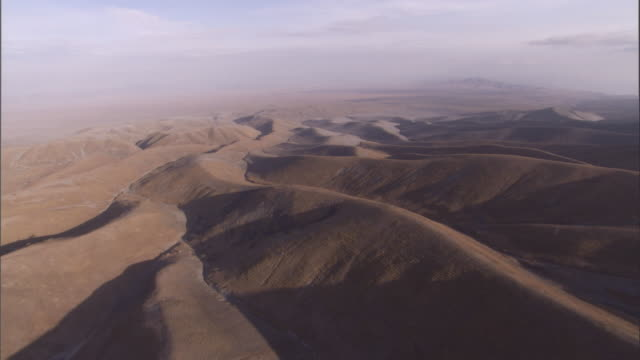 Hazy valleys and mountain ridges surround the Serengeti. Available in HD.
