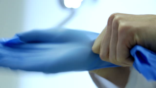 hd: putting on surgery gloves - stock video - scrubs stock videos & royalty-free footage