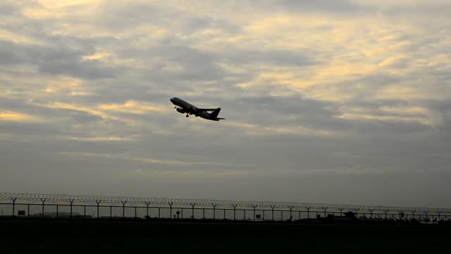 HD: avião descolar do aeroporto ao pôr do sol tempo