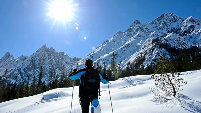 hd: alpinist le camminate con le racchette da neve in montagna contro luce solare - bastoncino da sci video stock e b–roll