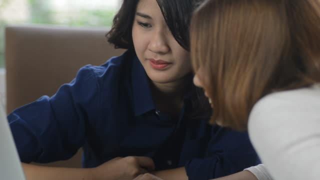 vidéos et rushes de hd :  look filles asiatiques sur un ordinateur portable - cartable
