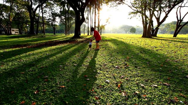 HD: Asiatische Mutter helfen Kind Spaziergang im park.