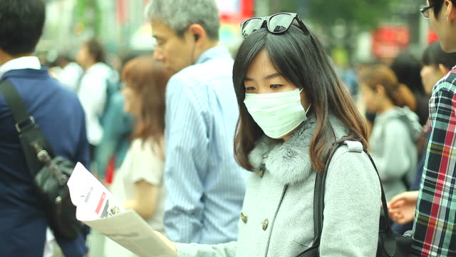 HD:Asian woman wearing a mask standing in a big city.