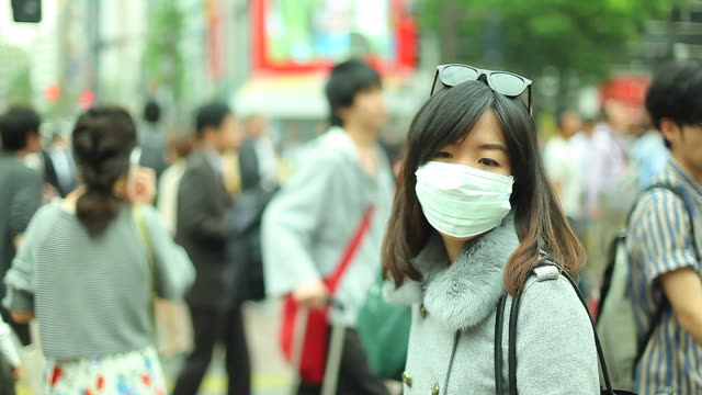 hd:asian woman wearing a mask standing in a big city. - epidemi bildbanksvideor och videomaterial från bakom kulisserna