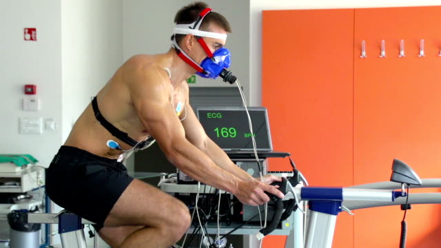 hd:athlete performing ecg and vo2 test on bicycle - test drive stock videos & royalty-free footage