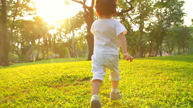 hd:baby boy running at the park during sunset. - baby boys stock videos & royalty-free footage