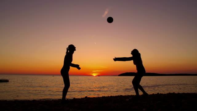 HD: Schöne Frauen spielen Sie Volleyball am Strand bei Sonnenuntergang