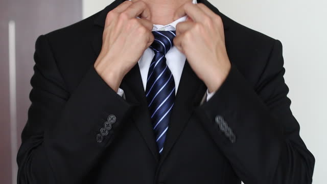 HD:Businessman correcting a tie.