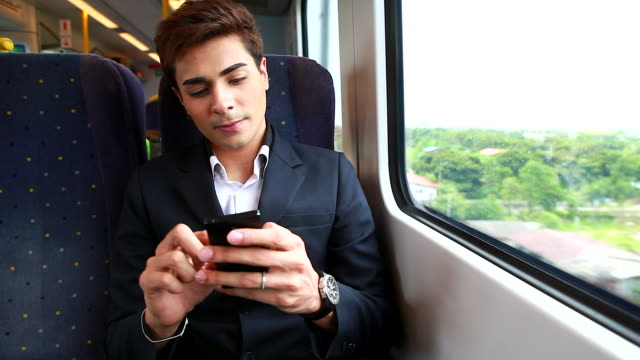 HD:Businessman playing mobile phone on the train.