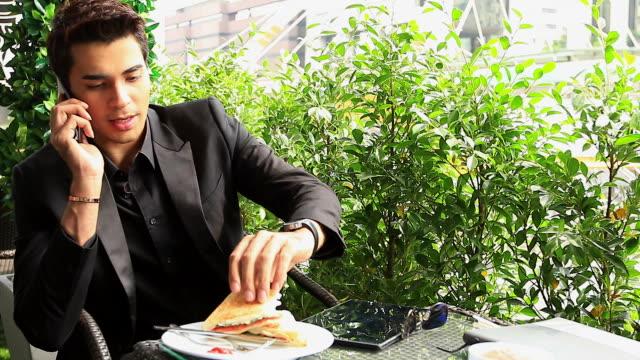 vídeos de stock, filmes e b-roll de hd: empresário falando no celular durante a refeição ao ar livre - bem vestido