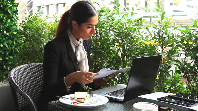 HD:Businesswoman working and eating breakfast outdoor.