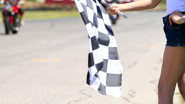 hd: hand der frau winkt race flagge. - beenden stock-videos und b-roll-filmmaterial