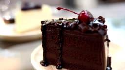 HD:Hand pouring sauce on  a piece of cake ,chocolate cake