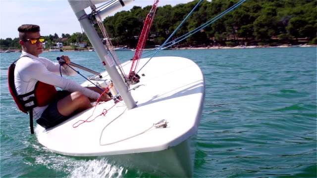 hd-handheld: shot of young man sailing on laser class boat - sailing boat stock videos & royalty-free footage