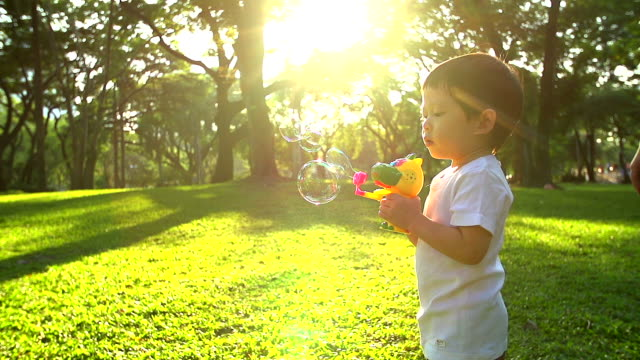 HD:Little boy in the sunset play soap bubbles.