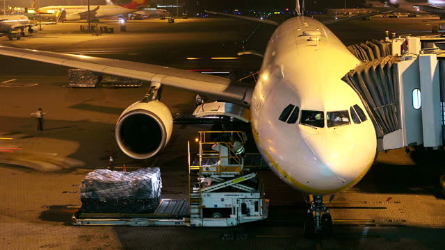 HD:Loading cargo operation for commercial airplane at night.