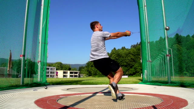 hd:locked down, shot of male hammer thrower in action - young men stock videos & royalty-free footage